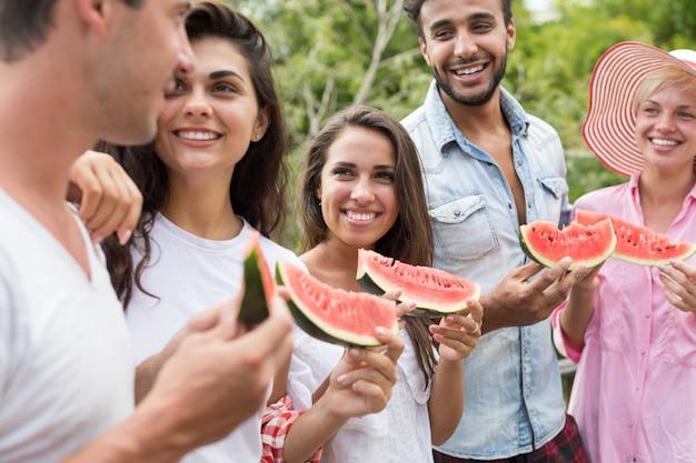 Heureux jeune groupe d'amis parlant tenir la tranche de pastèque