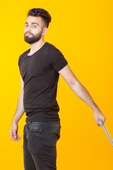 Heureux jeune hipster mâle avec une barbe tenant une valise jaune sur un mur jaune et se réjouissant de vacances. concept de voyage et de tourisme. place pour la promo