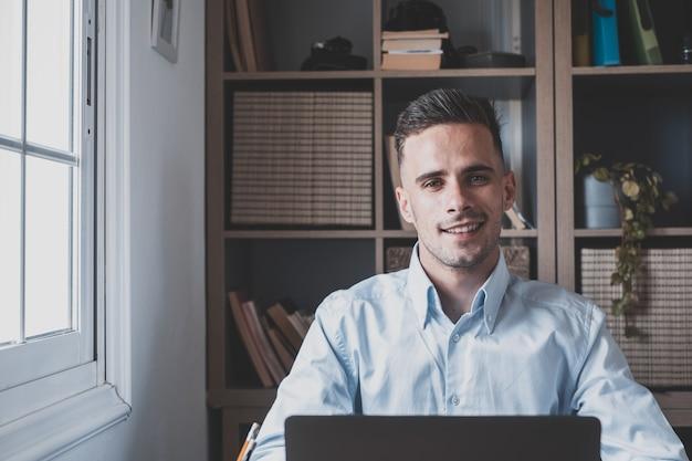Heureux jeune homme adolescent souriant et parlant en vidéoconférence étudiant et apprenant en ligne avec l'école. millennial fait ses devoirs à la maison en appelant