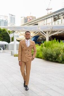 Heureux jeune homme d'affaires africain beau marchant dans les rues de la ville