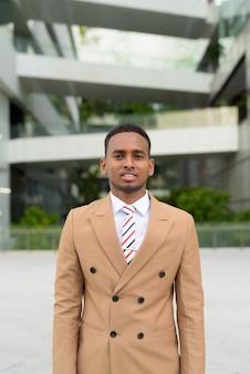 Heureux jeune homme d'affaires africain beau souriant dans les rues de la ville