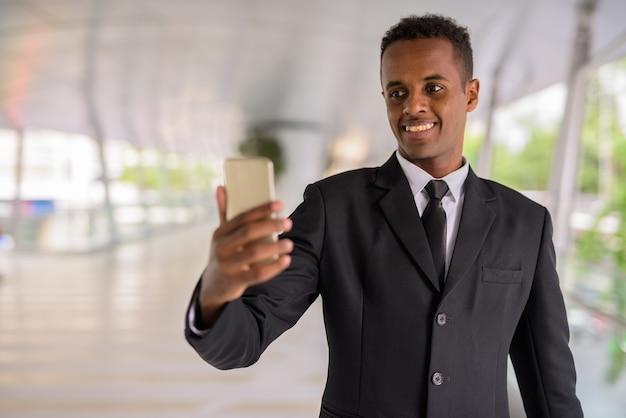 Heureux jeune homme d'affaires africain prospère utilisant un téléphone mobile à l'extérieur