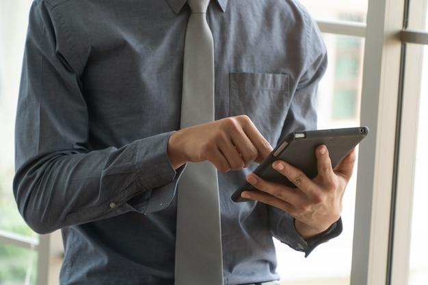 Heureux jeune homme d'affaires à l'aide de tablette numérique
