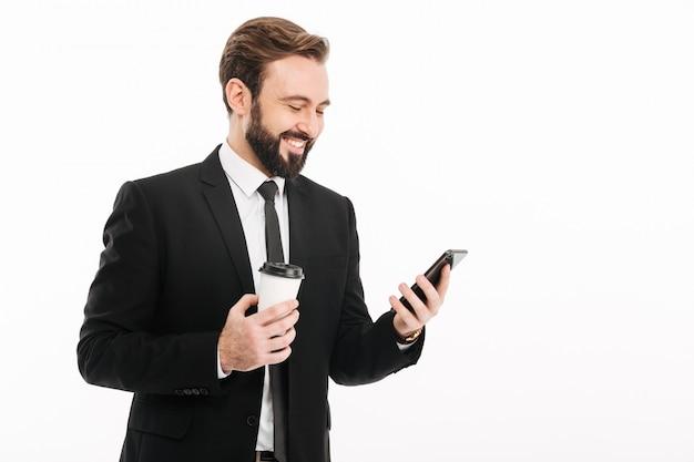 Heureux jeune homme d'affaires à l'aide de téléphone portable, boire du café.