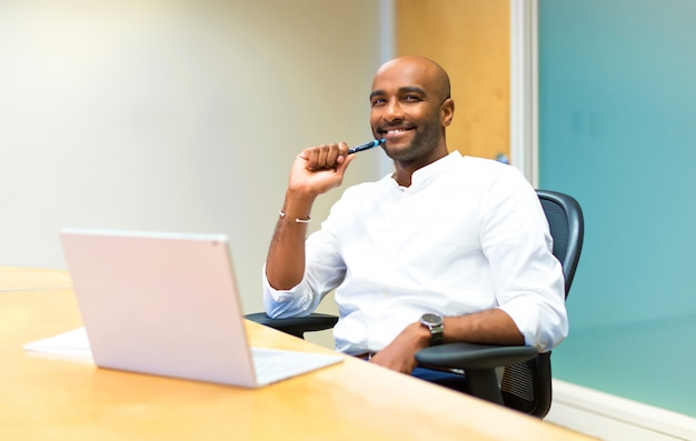 Heureux jeune homme d'affaires américain afro au bureau avec son ordinateur portable