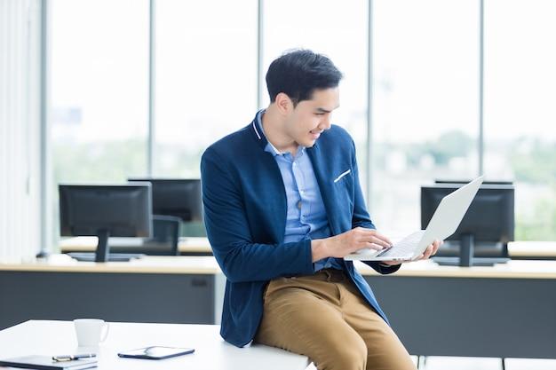 Heureux jeune homme d'affaires asiatique travaillant avec un ordinateur portable assis sur la table au bureau
