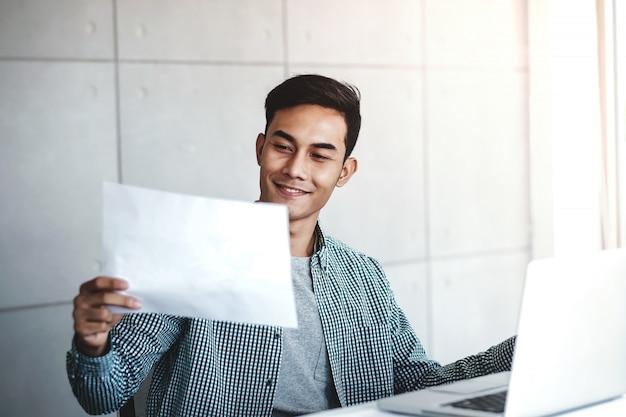 Heureux jeune homme d'affaires asiatique travaillant sur ordinateur portable.