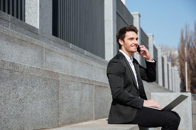 Heureux jeune homme d'affaires assis à l'extérieur parler par téléphone.