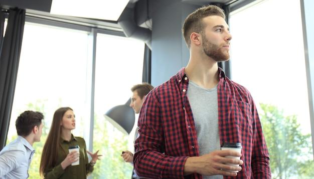 Heureux jeune homme d'affaires attrayant, boire du café au bureau.