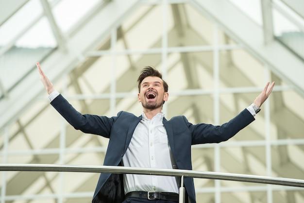Heureux jeune homme d'affaires au travail dans les bureaux modernes.