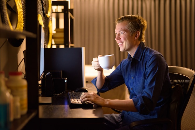 Heureux jeune homme d'affaires beau boire du café tout en travaillant des heures supplémentaires à la maison