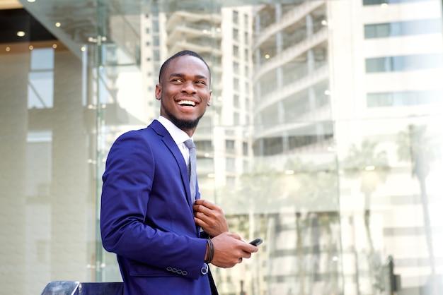 Heureux jeune homme d'affaires debout dans la ville