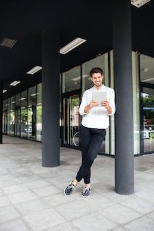 Heureux jeune homme d'affaires debout près du centre d'affaires et utilisant une tablette