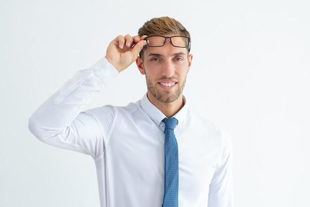 Heureux jeune homme d'affaires élever des lunettes