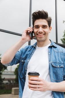 Heureux jeune homme d'affaires incroyable posant à l'extérieur à l'extérieur en marchant en parlant par téléphone portable en buvant du café.