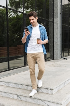 Heureux jeune homme d'affaires incroyable posant à l'extérieur à l'extérieur de la marche en discutant par téléphone portable en buvant du café.