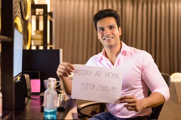 Heureux jeune homme d'affaires indien montrant rester à la maison signer tout en travaillant des heures supplémentaires à la maison pendant la quarantaine