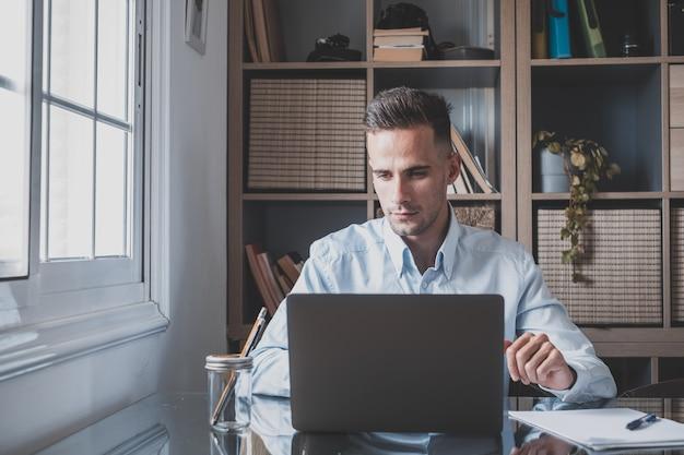 Heureux jeune homme d'affaires millénaire caucasien travaillant à la maison au bureau avec un ordinateur portable ou un ordinateur s'amusant. jeune homme en vidéoconférence prenant soin de l'entreprise ou du marché.