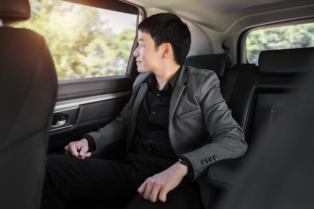 Heureux jeune homme d'affaires pensant et regardant par la fenêtre alors qu'il était assis sur le siège arrière de la voiture