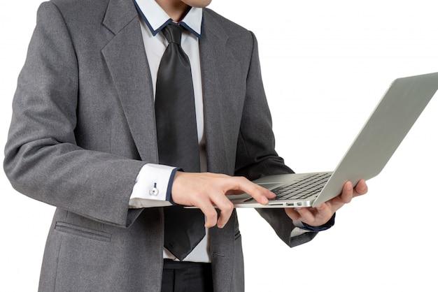 Heureux jeune homme d'affaires permanent tenir portable en costume, concept isolé
