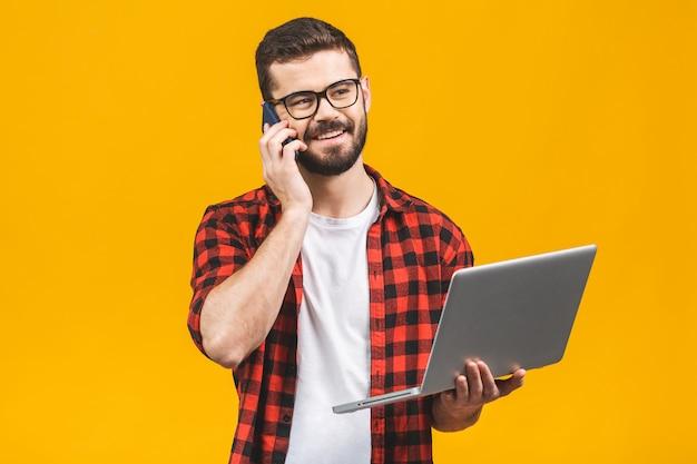 Heureux jeune homme d'affaires souriant en tissu décontracté avec un ordinateur portable appelant au téléphone