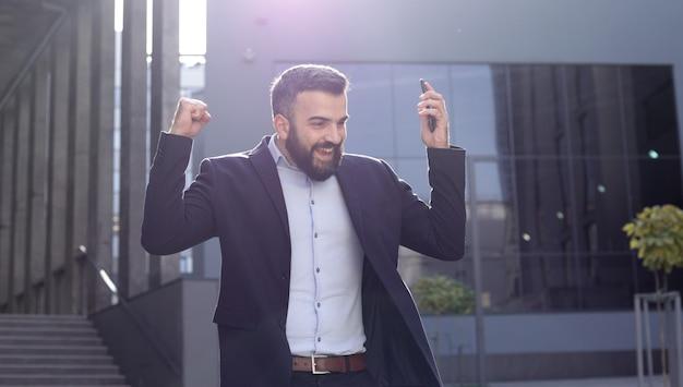 Heureux jeune homme d'affaires surpris par la bonne nouvelle et faisant oui le geste en regardant le smartphone