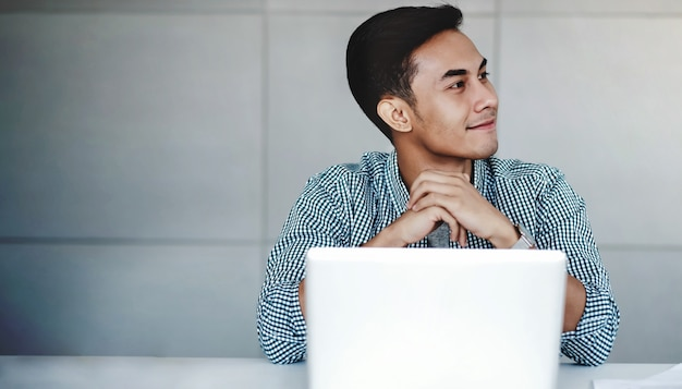 Heureux jeune homme d'affaires travaillant sur un ordinateur portable au bureau