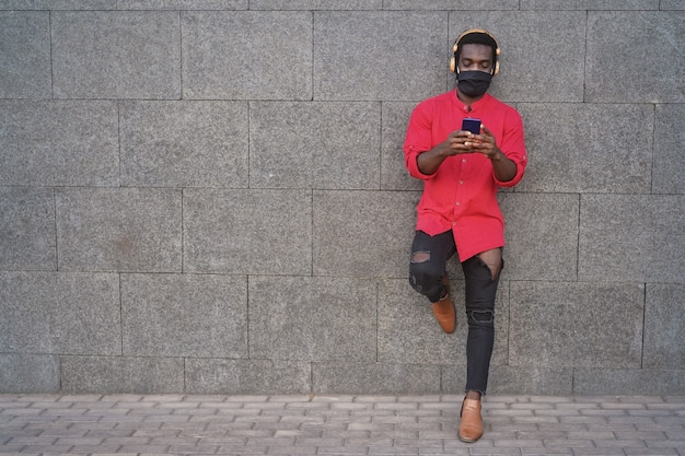 Heureux jeune homme africain écouter de la musique avec des écouteurs à l'extérieur tout en portant un masque de sécurité - focus sur le visage
