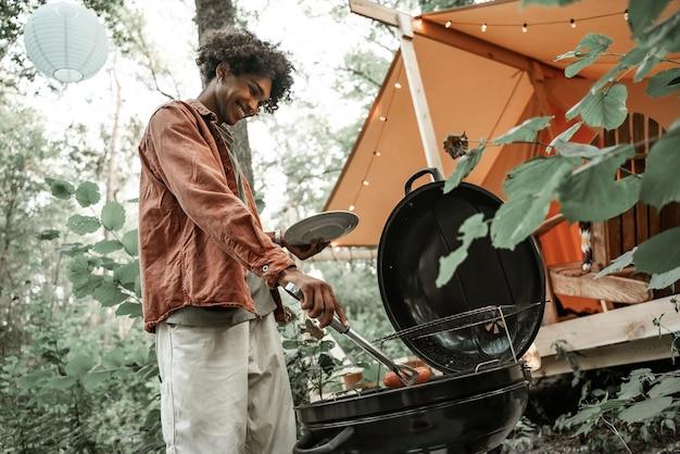 Heureux jeune homme africain grillant des saucisses, faisant un barbecue pour des amis dans la forêt en glamping. loisirs de plein air. après le confinement, rassemblement social. soirée barbecue, millénaires se reposant à l'extérieur du camping