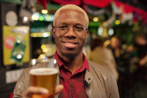 Heureux jeune homme africain à lunettes et vêtements décontractés vous regarde avec le sourire tout en grillant avec un verre de bière devant la caméra