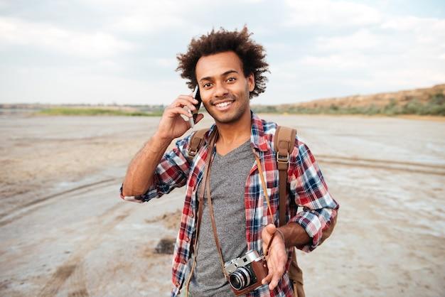 Heureux jeune homme africain avec photo vintage devant parlant sur téléphone portable à l'extérieur