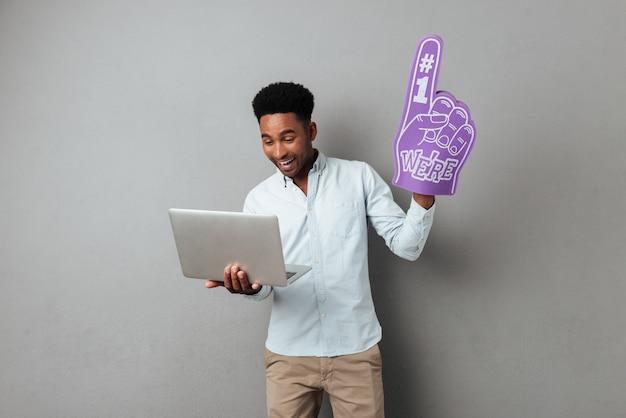 Heureux jeune homme africain regardant l'écran d'ordinateur portable