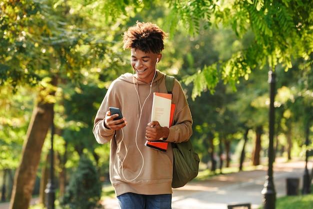 Heureux jeune homme africain avec sac à dos marchant