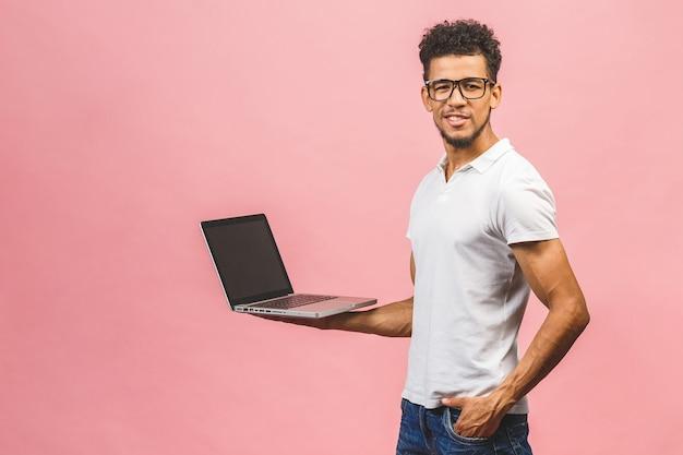 Heureux jeune homme afro-américain à l'aide d'un ordinateur portable