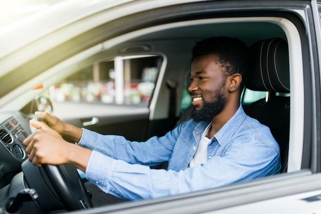 Heureux jeune homme afro-américain au volant d'une voiture sur les routes de la rue