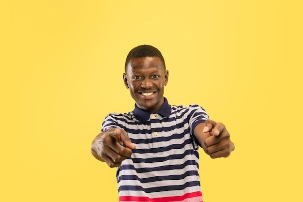 Heureux jeune homme afro-américain pointant sur spectateur isolé sur fond de studio jaune