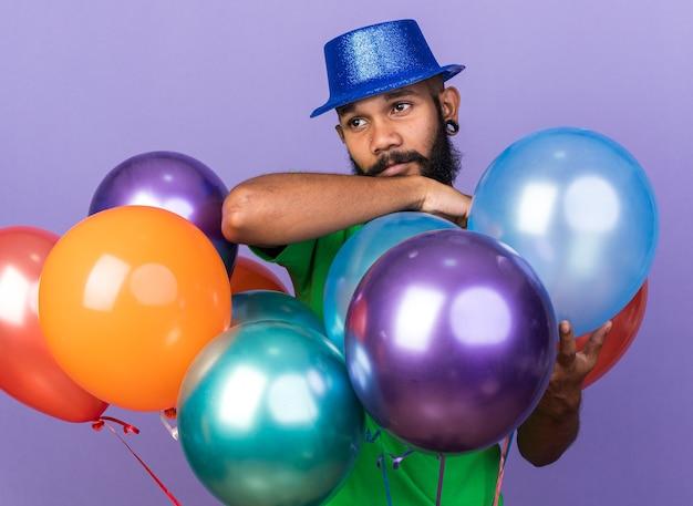 Heureux jeune homme afro-américain portant un chapeau de fête debout derrière des ballons isolés sur un mur bleu