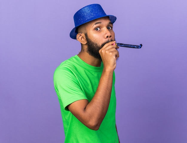 Heureux jeune homme afro-américain portant un chapeau de fête soufflant un sifflet de fête