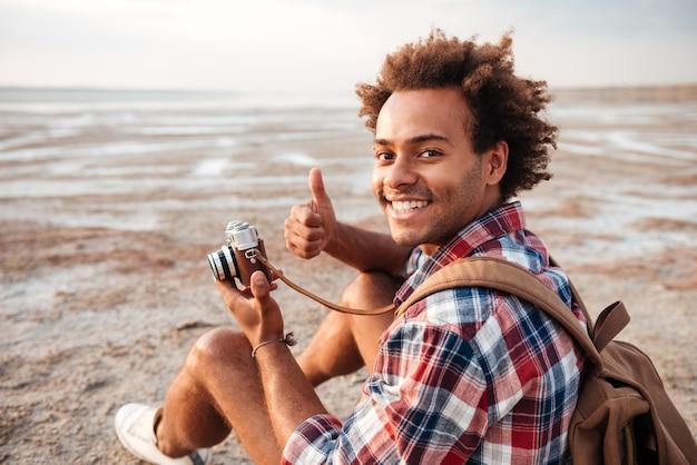 Heureux jeune homme afro-américain avec sac à dos prenant des photos et montrant les pouces vers le haut sur la plage