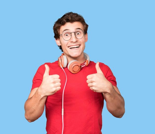 Heureux jeune homme à l'aide d'écouteurs et d'un smartphone avec un geste correct