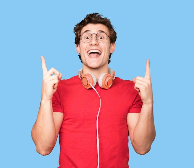 Heureux jeune homme à l'aide d'écouteurs et d'un smartphone et pointant vers le haut