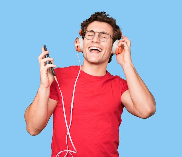 Heureux jeune homme à l'aide d'écouteurs et d'un smartphone
