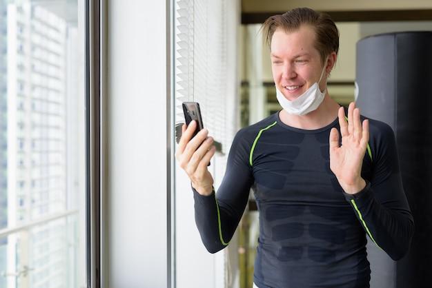 Heureux jeune homme avec appel vidéo masque et prêt à faire de l'exercice pendant le covid-19