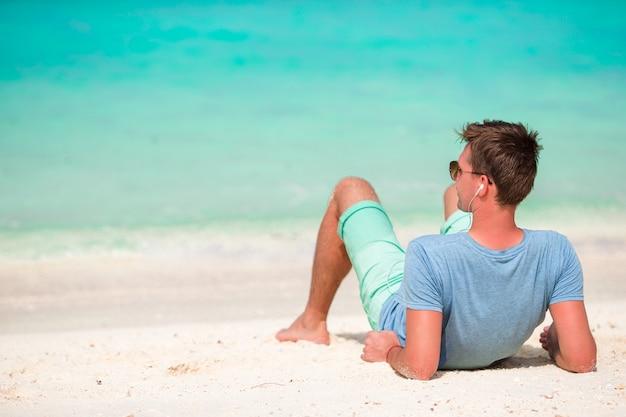 Heureux jeune homme appréciant le temps sur la plage de sable blanc