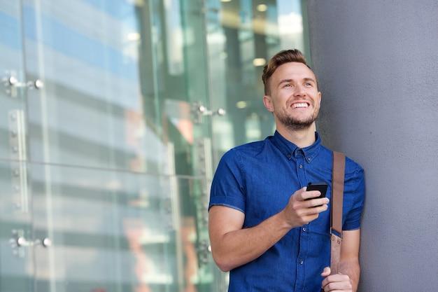 Heureux jeune homme appuyé contre le mur extérieur avec téléphone portable