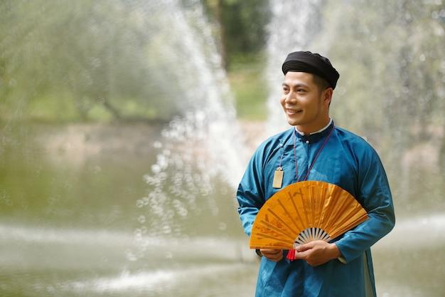 Heureux jeune homme asiatique en costume traditionnel vietnamien et casque debout près de la rivière avec un éventail de papier à la main et à l'écart