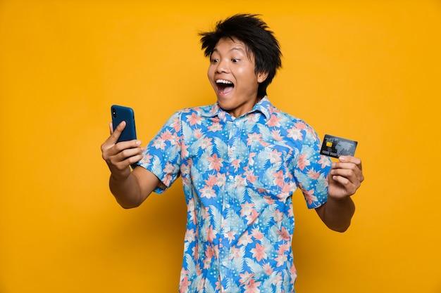 Heureux jeune homme asiatique debout isolé sur un espace jaune à l'aide de téléphone mobile tenant une carte de crédit.
