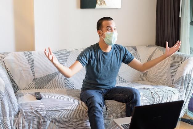Heureux jeune homme asiatique avec masque à regarder la télévision et obtenir de bonnes nouvelles à la maison en quarantaine