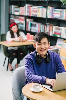 Heureux jeune homme asiatique mettant les mains sur le clavier de l'ordinateur portable et souriant alors qu'il était assis dans le cybercafé avec une tasse de café