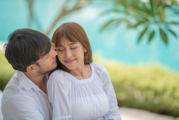 Heureux jeune homme asiatique picore sur la joue de sa petite amie